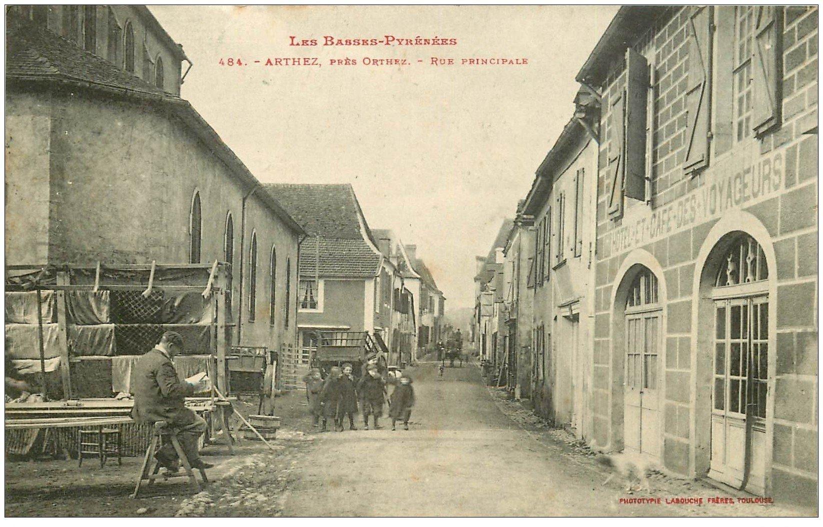 carte postale ancienne 64 ARTHEZ. Vendeur de Tissus Rue Principale. Hôtel Café des Voyageurs 1910