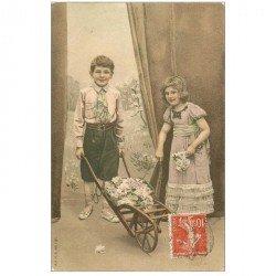 carte postale ancienne ENFANTS. Jeunes gens avec une brouette pleine de Fleurs vers 1910